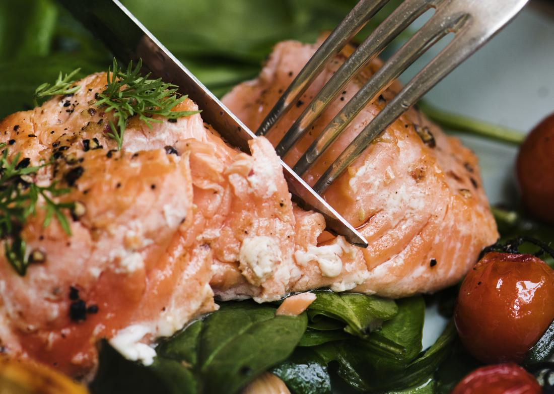 salmon-being-cut-with-a-knife-and-fork